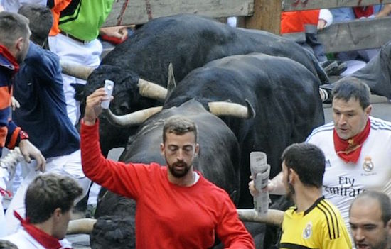 "A participant runs in front of Jandilla's bulls as he takes a ""selfie"" (photograph of himself) during the fifth bull-run of the San Fermin Festival in Pamplona, northern Spain, on July 11, 2014. Spanish authorities are cracking down on dare devils who shoot camera footage even as they risk their lives by running with half-tonne fighting bulls at the annual San Fermin festival. PHOTO/ RAFA RIVAS"